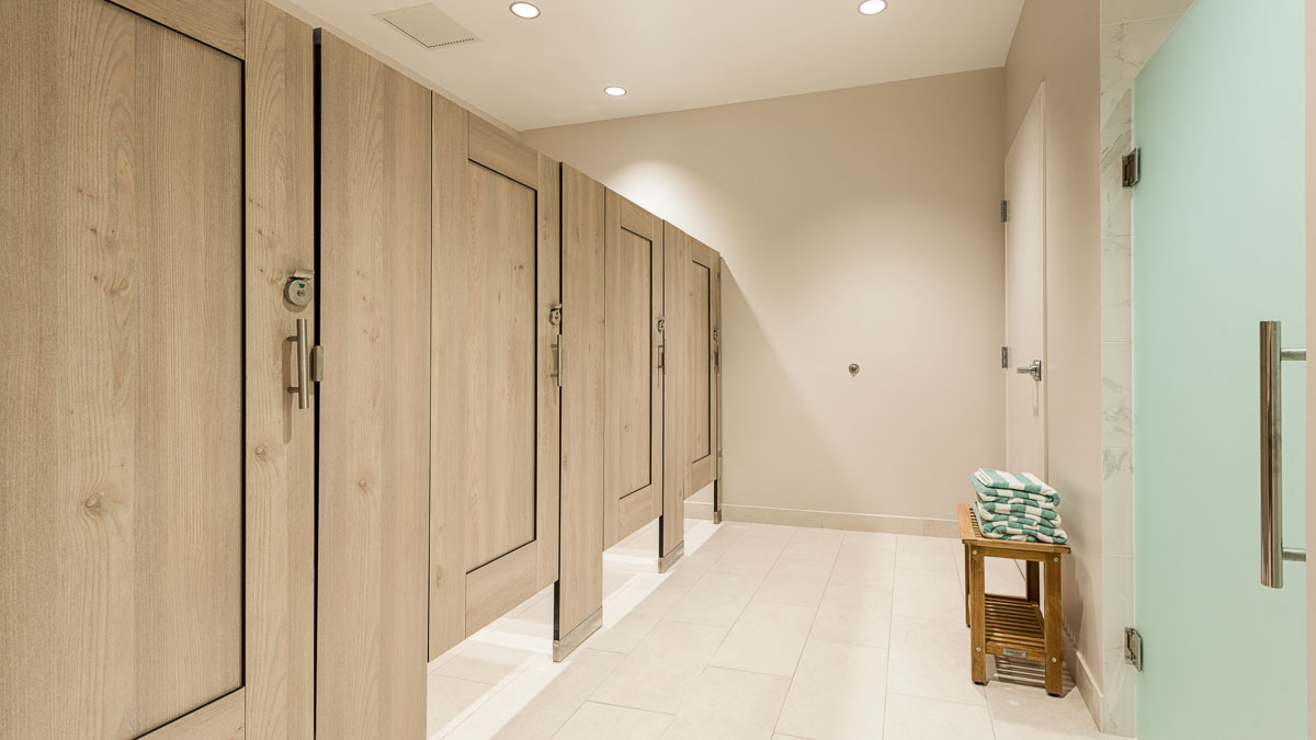 Country Club bathroom featuring compact laminate partitions with light tan, wood grain captured panel doors with frosted green shower door.