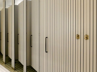 Large resort bathroom features six full size, grey compact laminate partitions and doors with vertical engraving that displays black lines.