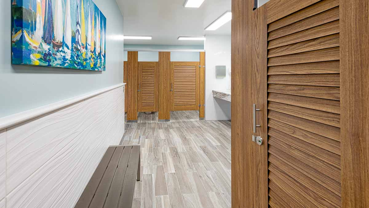 Marina bathroom features compact laminate, wood grain louver doors in headrail braced style. Sailboats print on wall above grey metal changing bench.