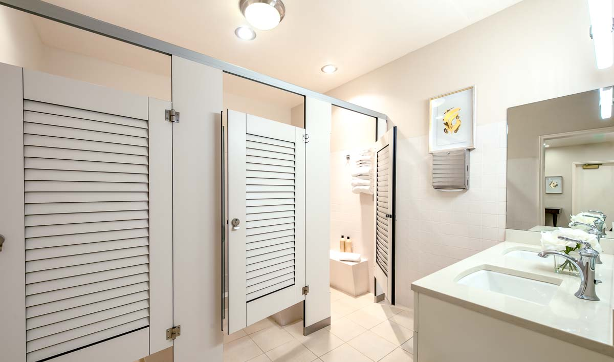 Country Club locker room with pretty white compact laminate louver doors opposite vanity and mirror. Open door shows changing area leading to shower.