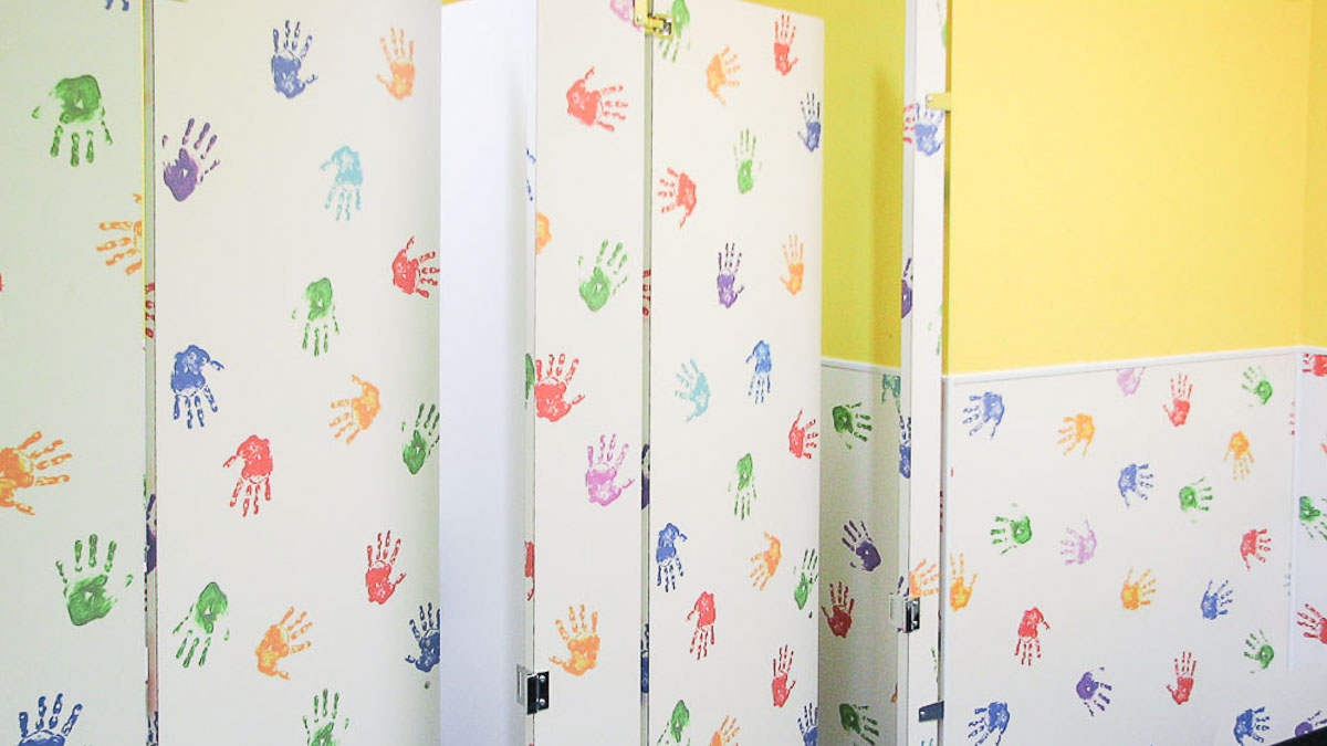 Preschool bathroom featuring white custom laminate with whimsical, colorful handprints on child size partition alongside matching wainscoting.