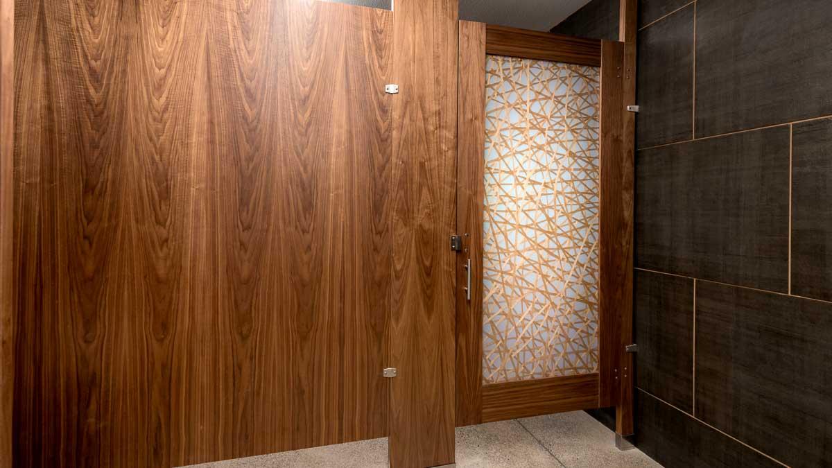 Full height, beautiful wood veneer panel with doorlite door presenting random crossing gold lines on white acrylic insert in rich green tile bathroom.