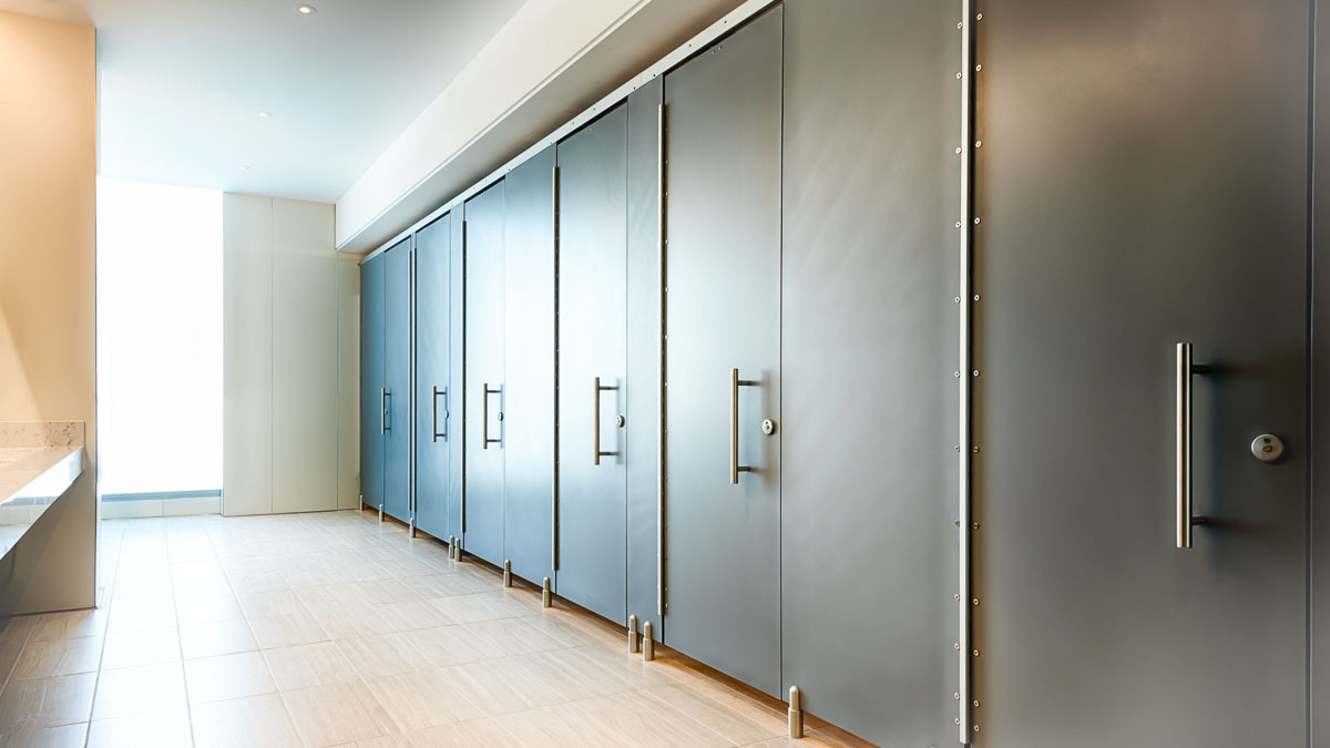"""Expansive executive bathroom with full privacy European zero sightline solid surface partitions featuring 16"""" stainless steel bar pulls."""