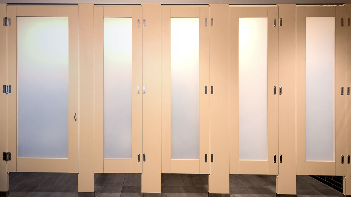 Laminate toilet partitions in French vanilla with frosted acrylic door lites showing no door gaps with zero sightline feature.