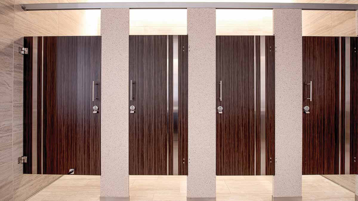 Stunning casino bathroom with solid surface pilasters and four plastic laminate dark, wood grain doors with vertical stainless steel insert strips.