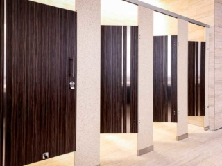 Majestic casino bathroom with solid surface pilasters and four plastic laminate wood grain opened doors with vertical stainless steel insert strips.