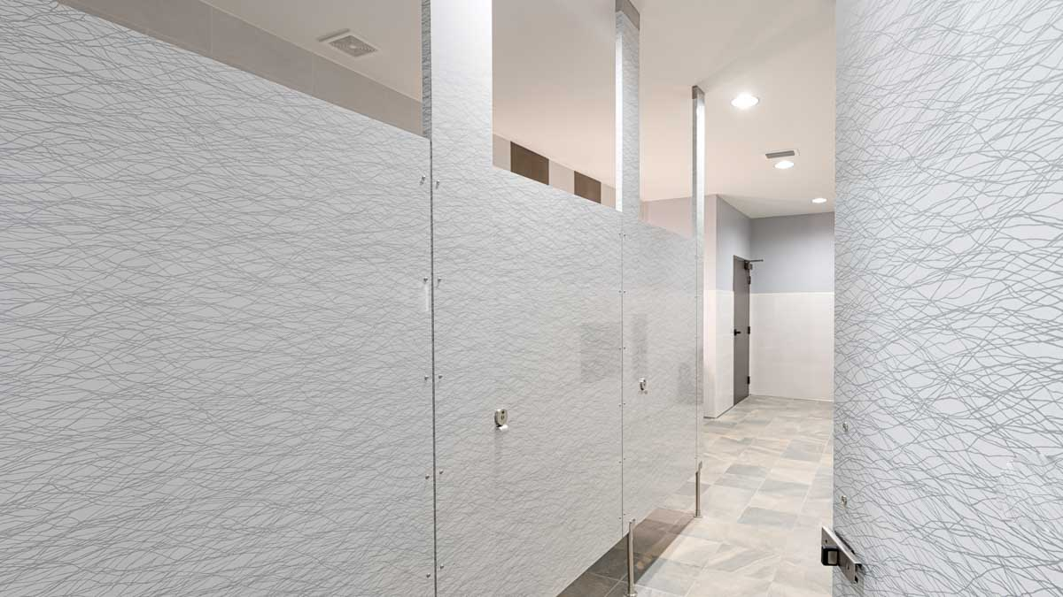 Four slab doors in gloss plastic laminate featuring wavy grey patterned lines on white background in modern university clubhouse bathroom.