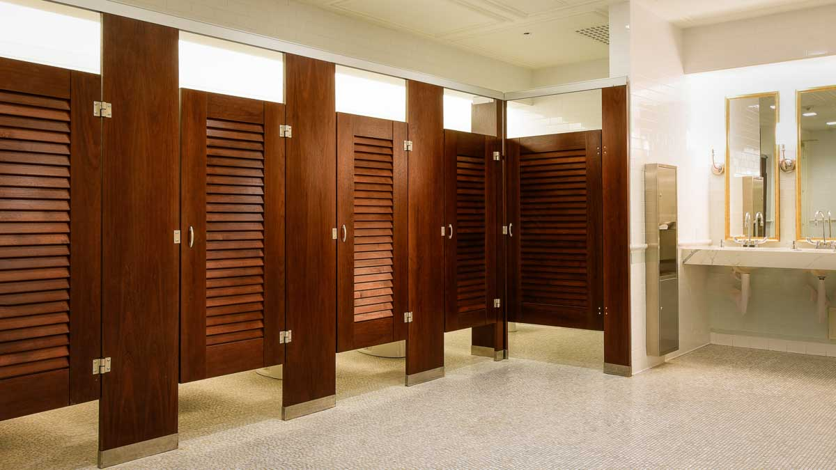 Elegant reception venue bathroom showing wood veneer pilasters and five louver doors in headrail braced style with gold rimmed mirrors over vanity.