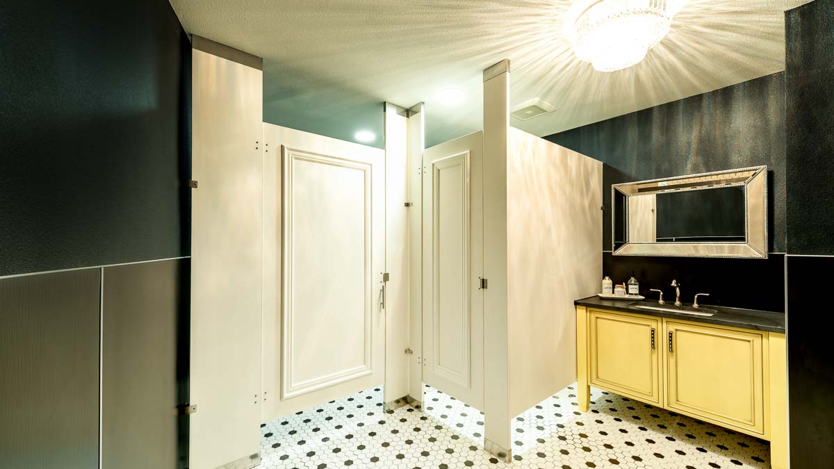 Designer showroom bathroom with white laminate partitions shows doors with picture frame molding. Yellow vanity, silver framed mirror and chandelier.