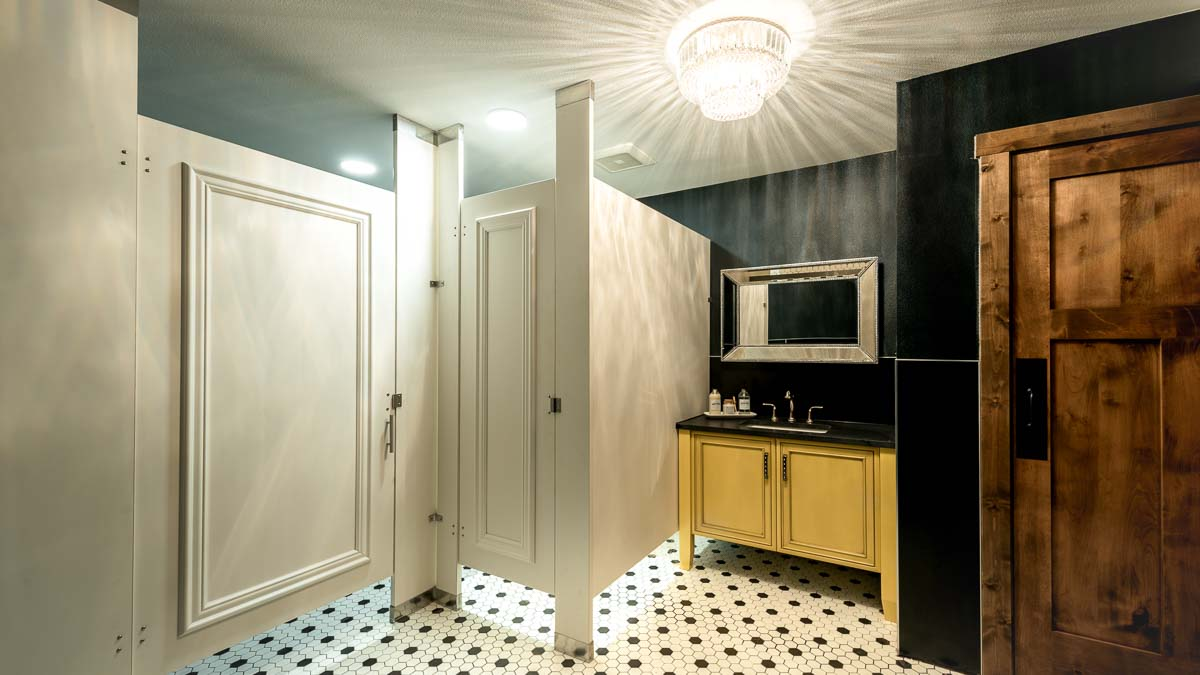 Designer showroom bathroom, white laminate partitions with picture frame molding in floor to ceiling style. Yellow vanity and crystal chandelier.