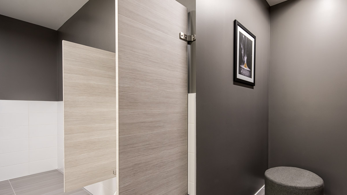 Dark grey walled men's bathroom including laminate privacy screens between urinals made with Laminart in textured grey hues.