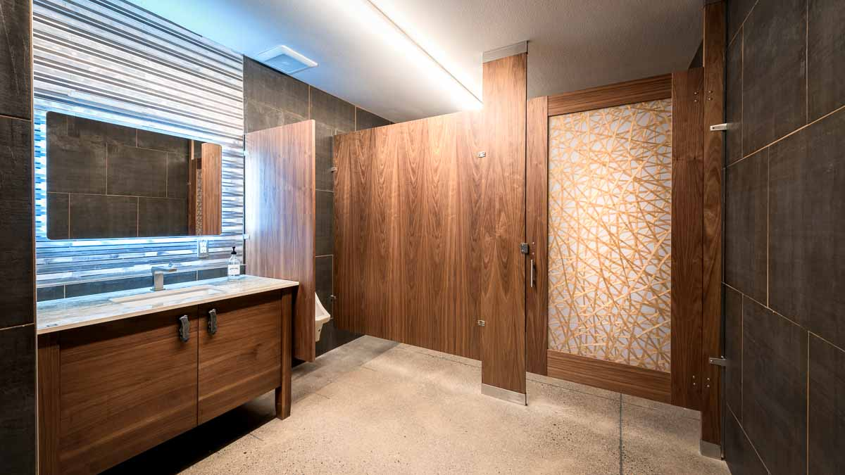 Beautiful wood veneer bathroom partition and acrylic insert door showing stray crossing gold lines and corrugated metal backsplash and cabinet vanity.