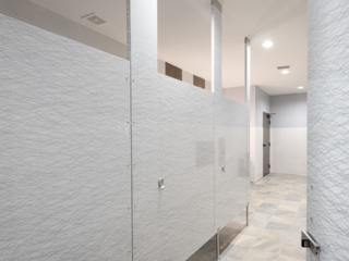 Modern university clubhouse bathroom features four slab doors in gloss plastic laminate featuring wavy grey patterned lines on white background.