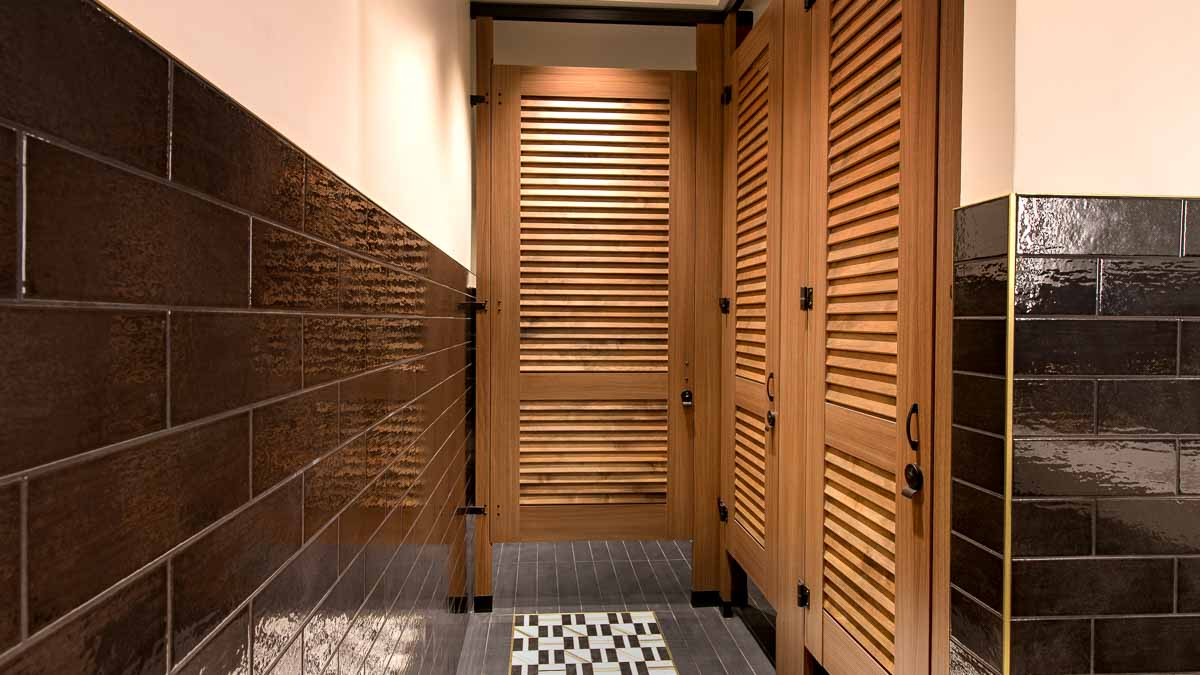 Trendy hotel bathroom with high privacy laminate wood grain partitions and three louver doors with powder coat hardware in dark subway tile bathroom.