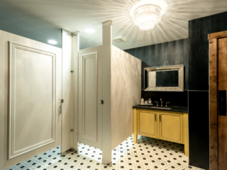 Designer showroom bathroom with white laminate partitions show doors with picture frame molding. Yellow vanity, silver framed mirror and chandelier.