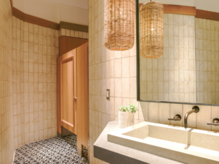 Trendy restaurant bathroom features tan tiled walls with one wood veneer partition and picture frame molding on door. Mirror and modern quartz sink.