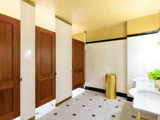 Swanky business headquarters tiled bathroom features engineered stone pilasters with three wood veneer, captured panel doors with bronzed hardware.