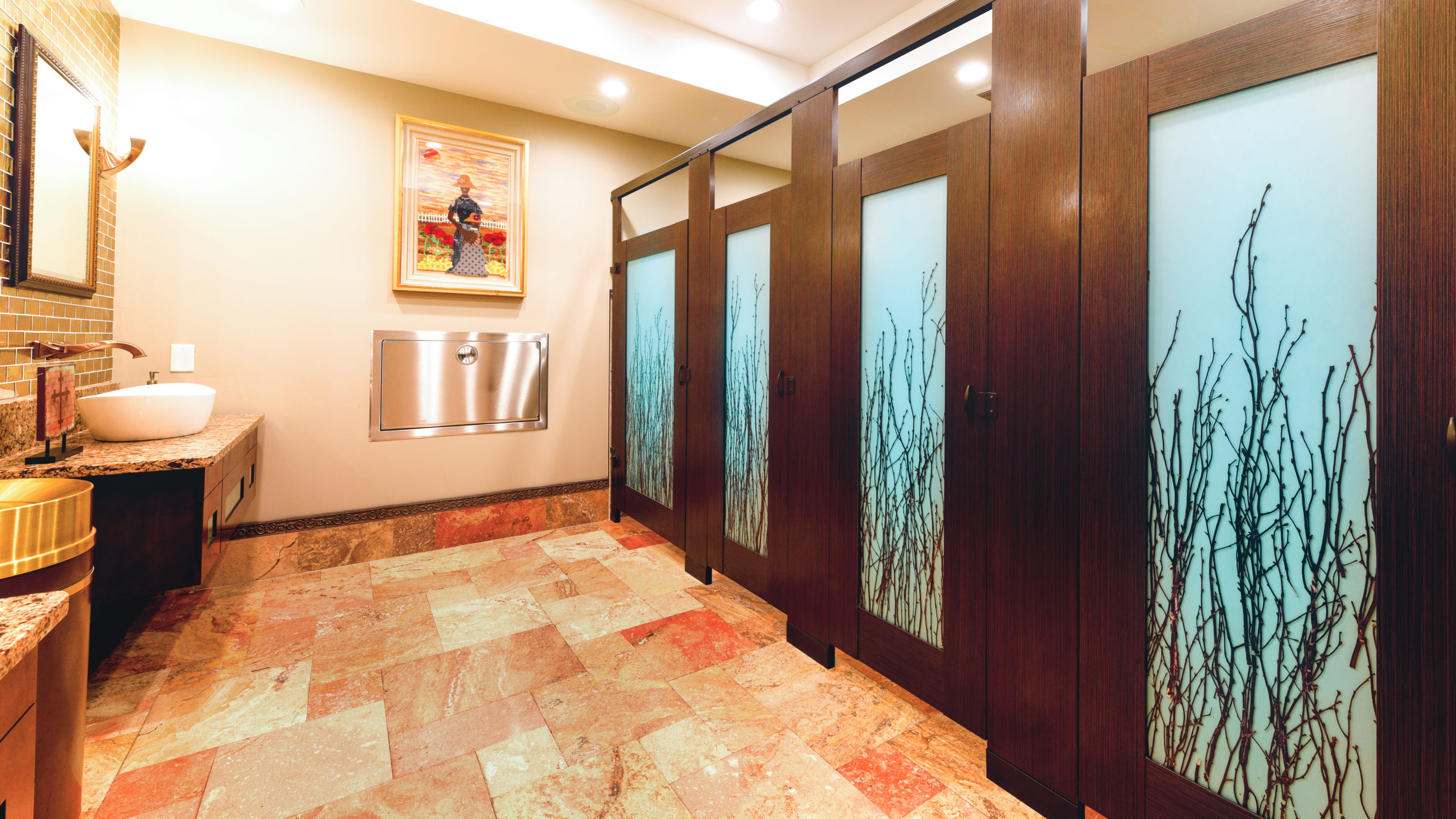 Glorious church restroom features brown laminate partitions and four doors with birch branch design on acrylic inserts. Bronzed fixtures and cross.