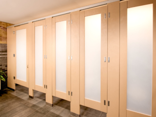 High privacy french vanilla plastic laminate bathroom partitions with luminous frosted acrylic door lite insert features zero sightline upgrade.
