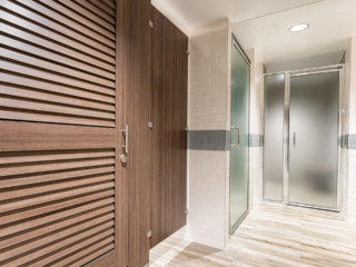 White tiled spa bathroom and shower featuring contrasting compact laminate partitions with traditional brown louver doors.
