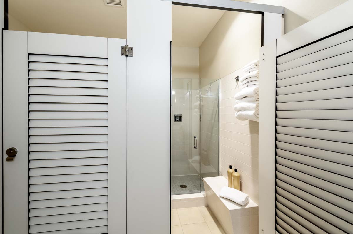 Two pretty, white compact laminate dressing compartments with louver doors. Open door shows changing area with bench leading to clear shower door.
