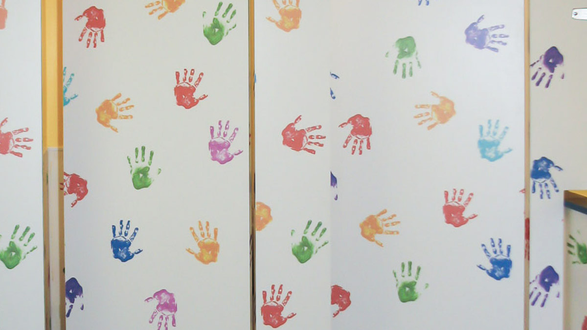 Close up view of preschool toilet partitions featuring white custom laminate with whimsical, colorful handprints on child size doors.
