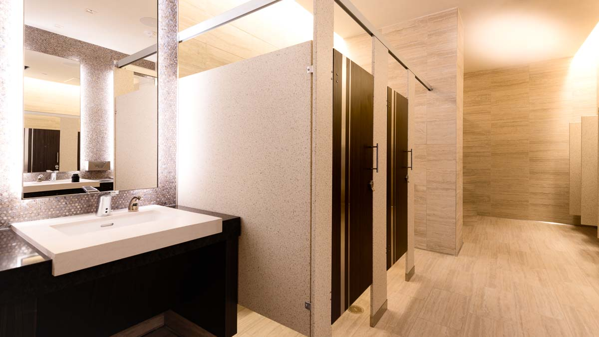 Variegated tan tiled wall and floor in luxurious bathroom with solid surface panels and two brown laminate doors with stainless steel inserts.