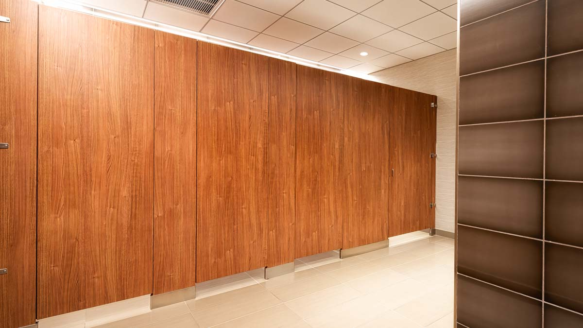 All gender bathroom features four full height compartments and zero sightline presents a homogeneous look in handsome, variegated brown laminate.