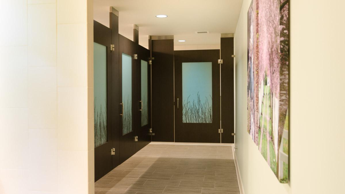 Ceiling hung wood veneer bathroom partitions spotlighting unique, custom birch branch design on frosted acrylic door lite inserts.