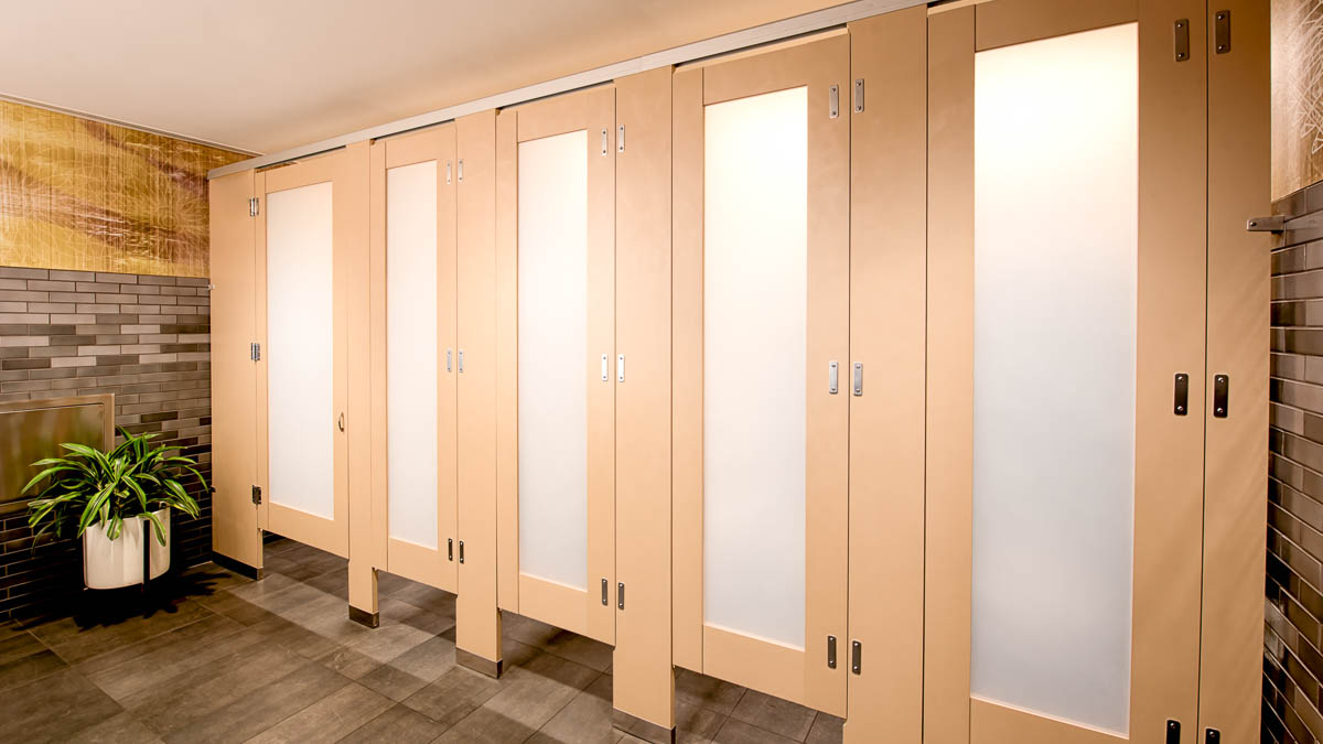French vanilla plastic laminate toilet partitions with luminous frosted with acrylic door lite insert. High privacy for hotel bathroom.
