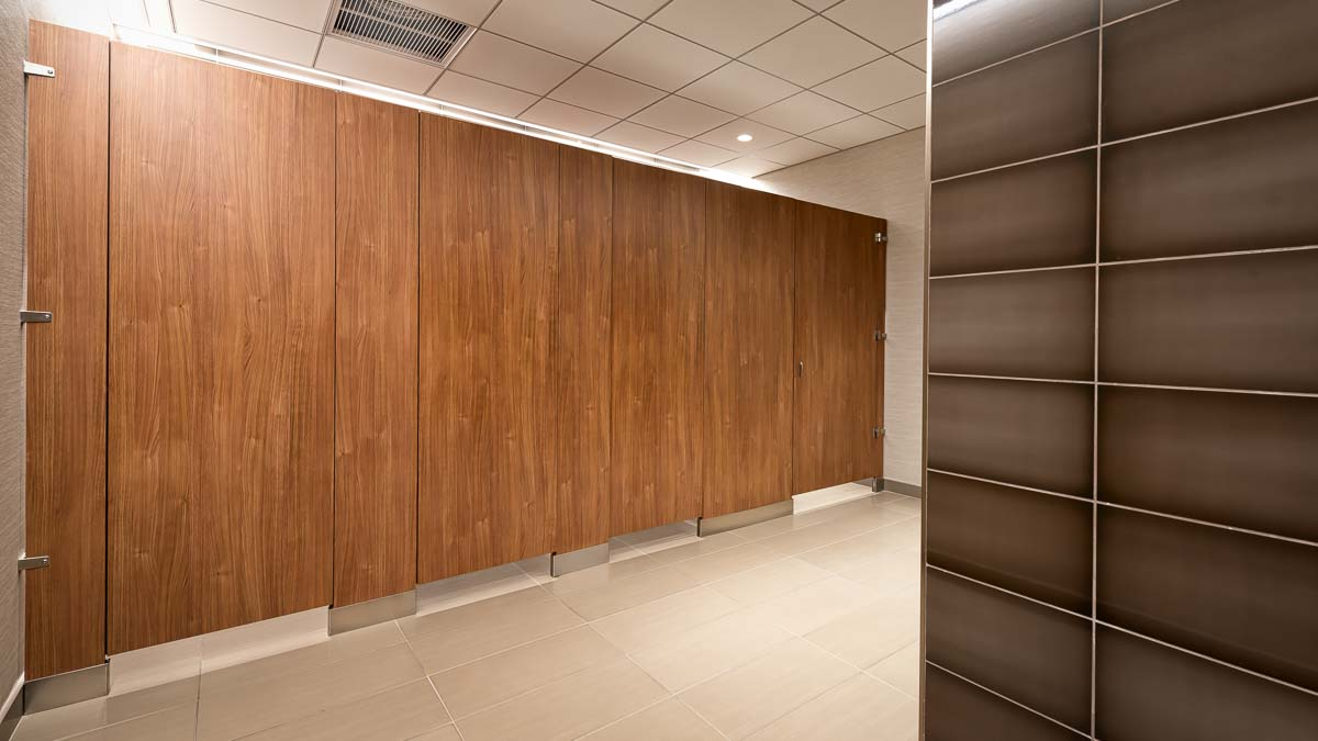 Variegated, brown plastic laminate, floor mount bathroom partitions with four full height, zero sightline feature doors for high privacy.