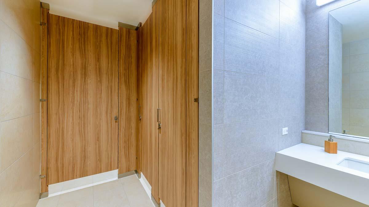 Three lavish, full height, vertical wood grain laminate slab bathroom doors with zero sightline feature in floor to ceiling style in tiled room.