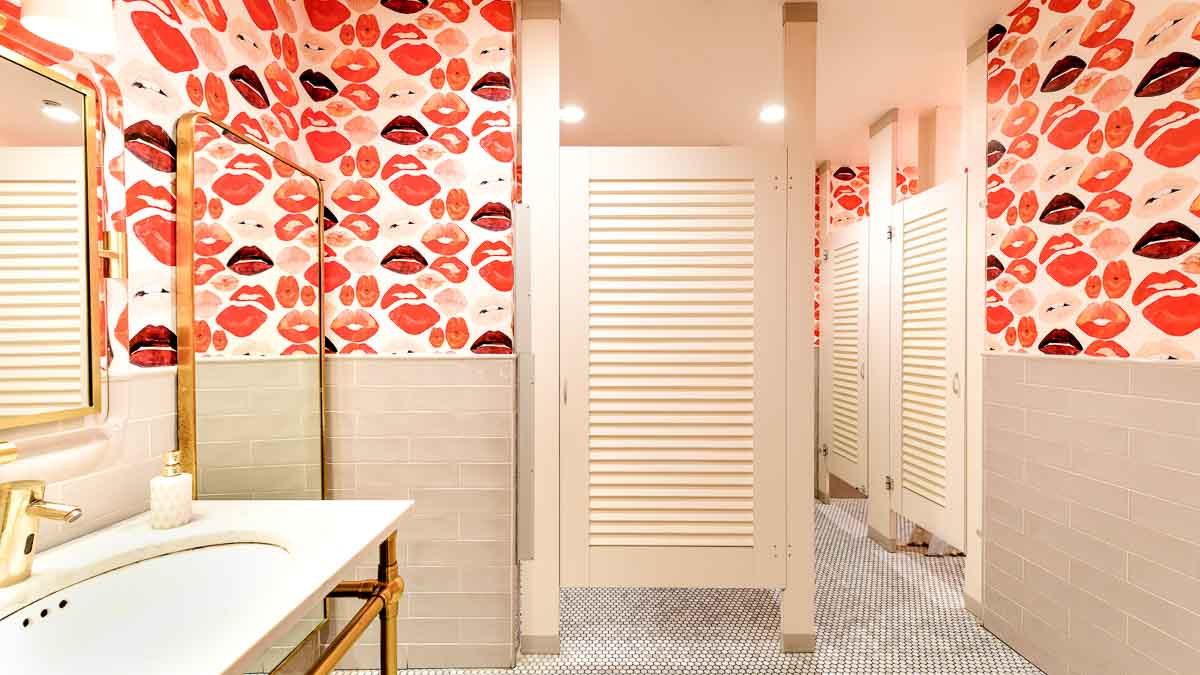 Wallpaper full of large red lips and cream subway tiles on wall showcase bright white laminate louver bathroom doors in trendy restaurant galleria.