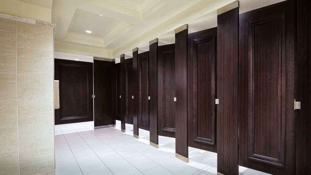 Seven, dark wood grain plastic laminate bathroom partitions and doors accentuating picture frame molding in floor to ceiling style. Coffered ceiling.