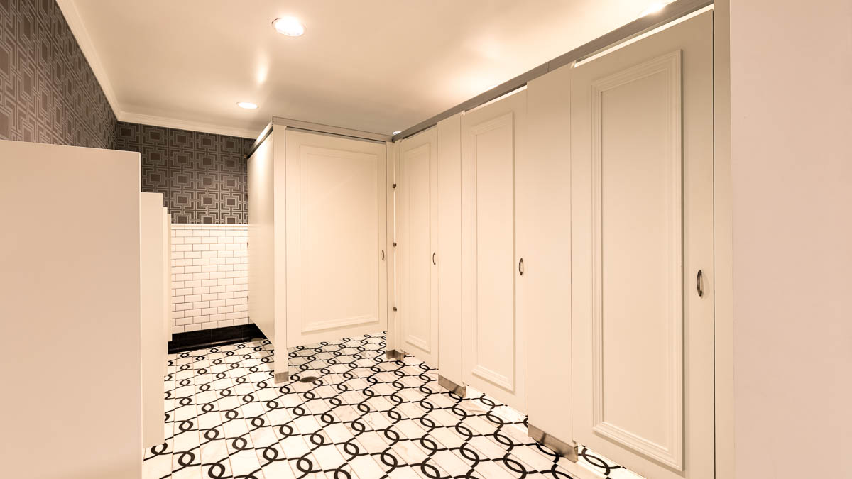 Grand, bright white hotel men's bathroom with four doors showing picture frame molding in headrail braced style. Geometric design on walls and floors.