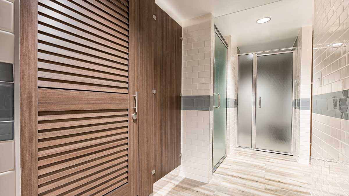 White tiled spa bathroom and shower presenting contrasting compact laminate partitions with warm brown louver doors.