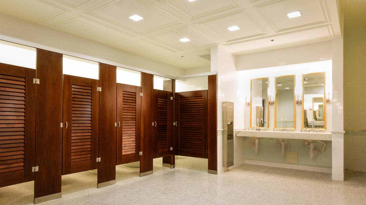 Elegant reception venue bathroom with coffered ceiling showing five wood veneer pilasters and louver doors with three gold rimmed mirrors over vanity.