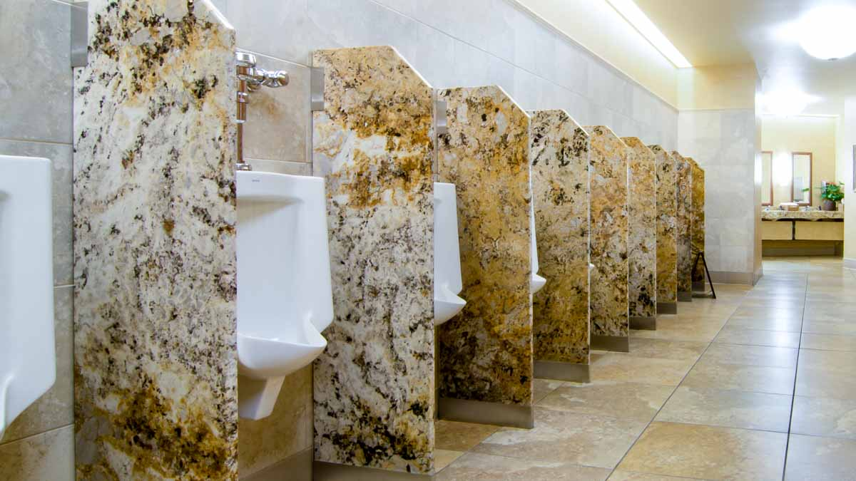 Nine brown, tan and white combined color engineer stone urinal privacy screens in impressive, large men's casino bathroom.