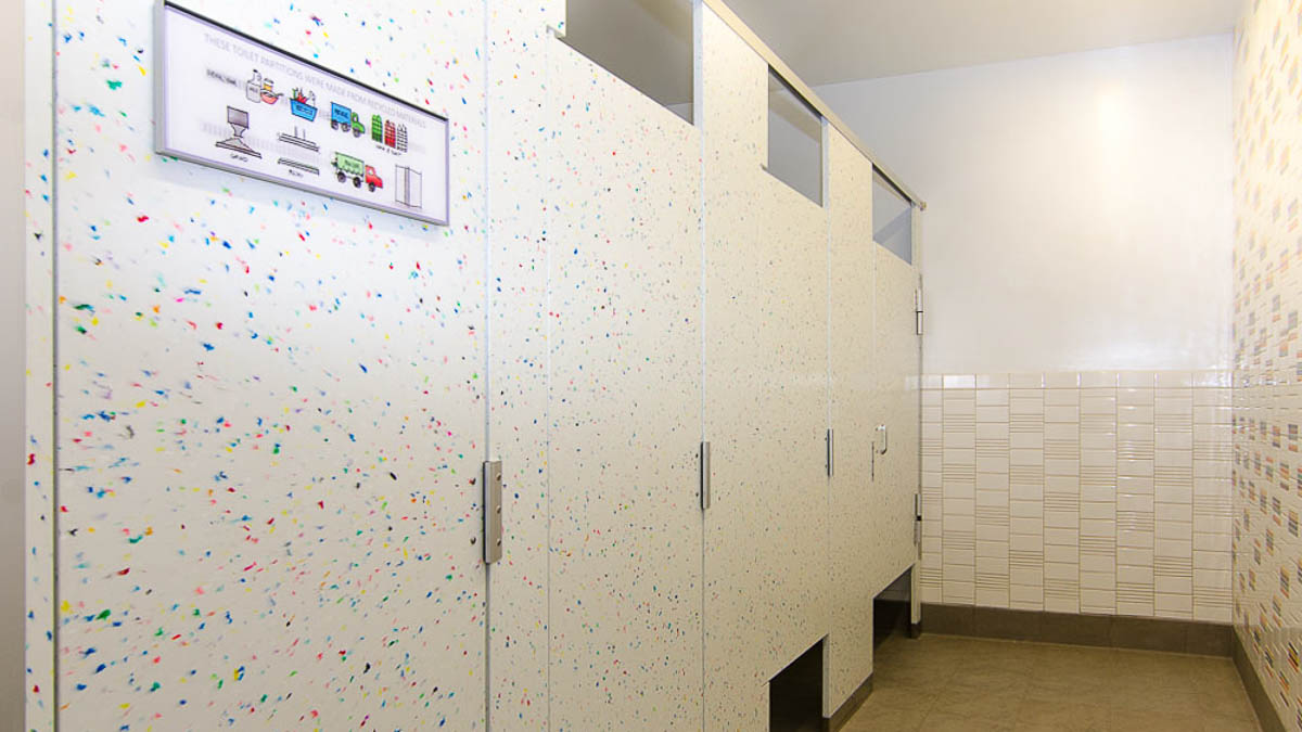 Bathroom partition featuring fun, multi-color speckles on white solid surface material. Colorful drawing on end door demonstrates recycling process.