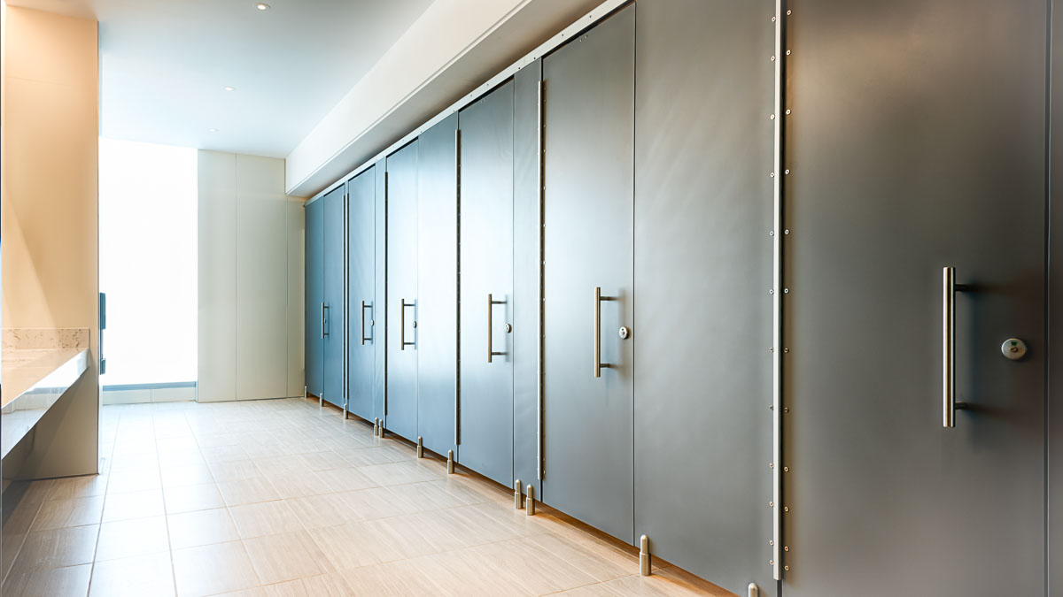 """Spacious executive bathroom with high privacy european style, zero sightline solid surface partitions featuring 16"""" stainless steel bar pulls."""