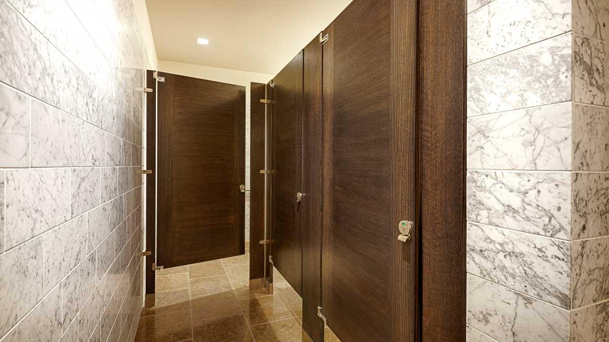 Elegant marble wall bathroom with three interesting contrasting grain, brown wood veneer door with inlay design.