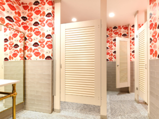 Trendy restaurant galleria bathroom shows wallpaper full of large red lips, cream subway tiles on wall showcases bright white laminate louver doors.