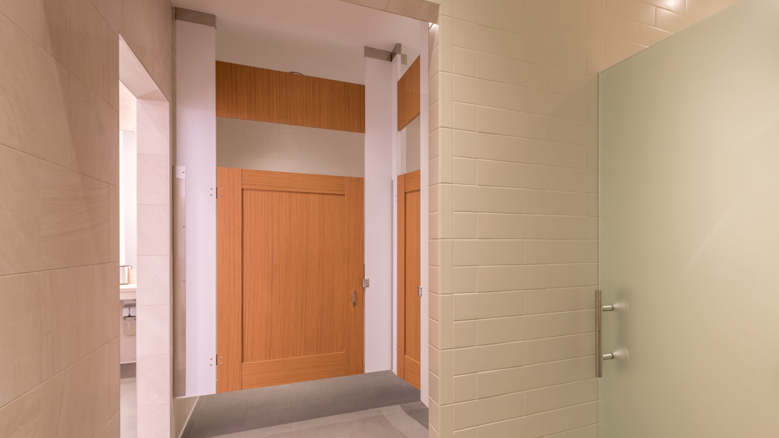 White subway tiled trendy business gym bathroom shows ceiling hung honey colored, wood grain captured panel doors with transom. Frosted shower door.