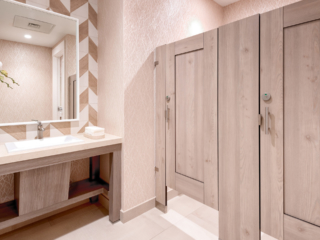 Country Club bathroom featuring compact laminate partitions with light tan, wood grain captured panel doors. Elegant vanity with chevron wallpaper.