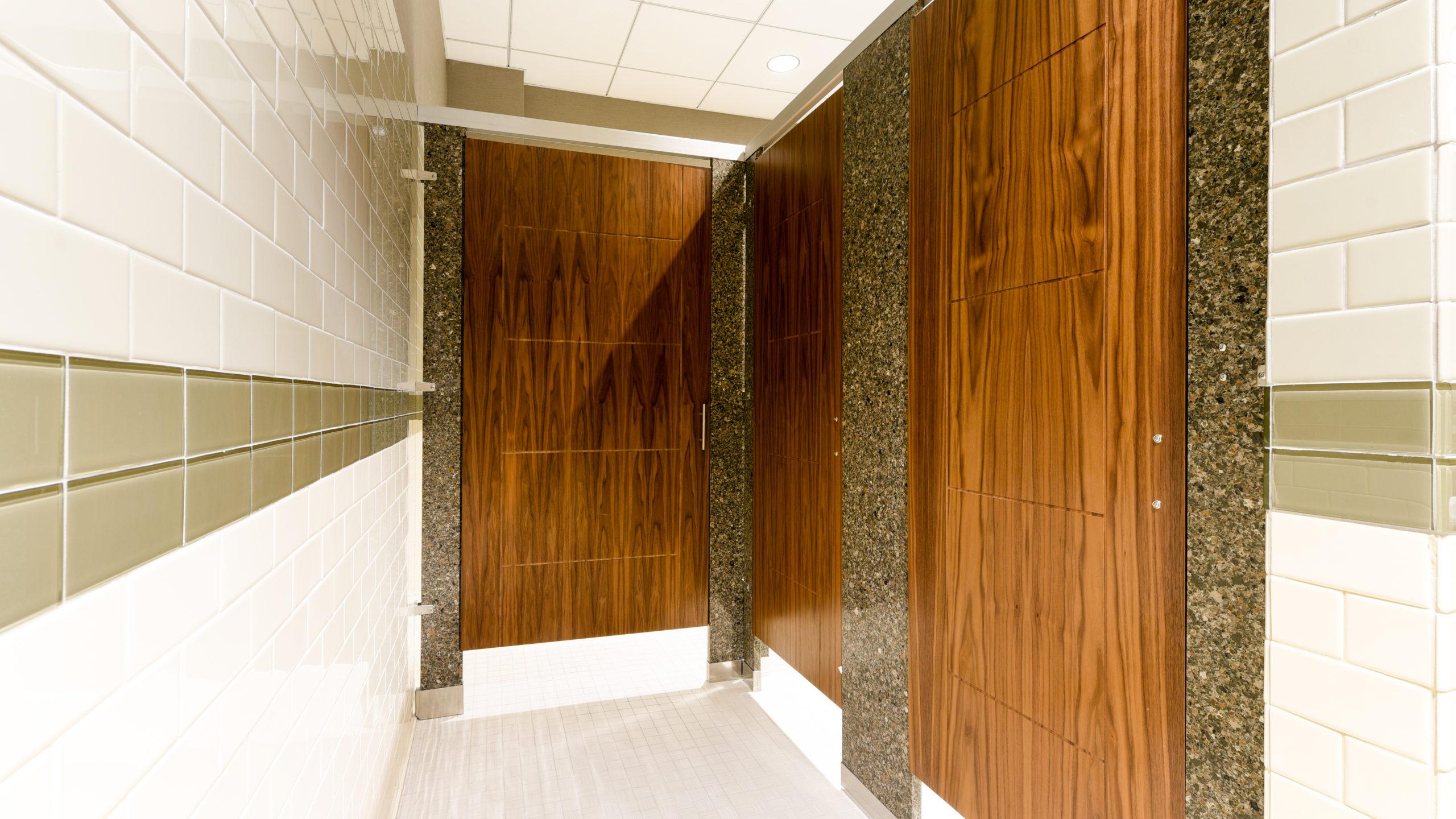 White subway tiled business showroom bathroom featuring three rich wood grain, engraved veneer doors with grey speckled engineered stone pilasters.