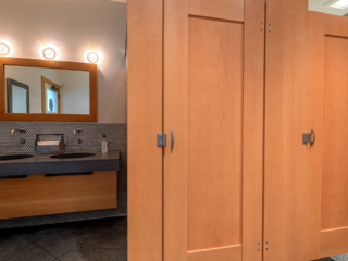 Craftsman style bathroom shows honey colored wood veneer partitions with two captured panel doors next to stone vanity and wood framed mirror.