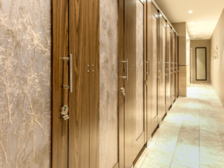 Expansive wildlife museum bathroom features eight, high privacy laminate doors with baby's breath design on translucent acrylic door lite inserts.