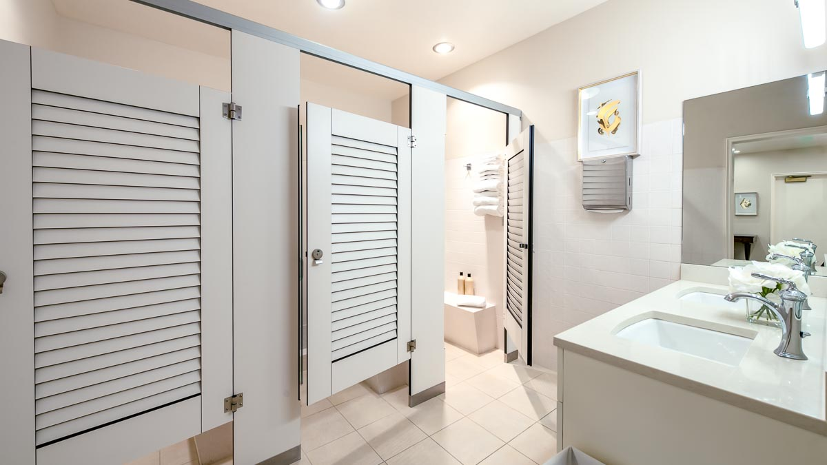 Three, pretty white compact laminate louver dressing compartments opposite vanity and mirror. Open door shows changing area with bench and towels.