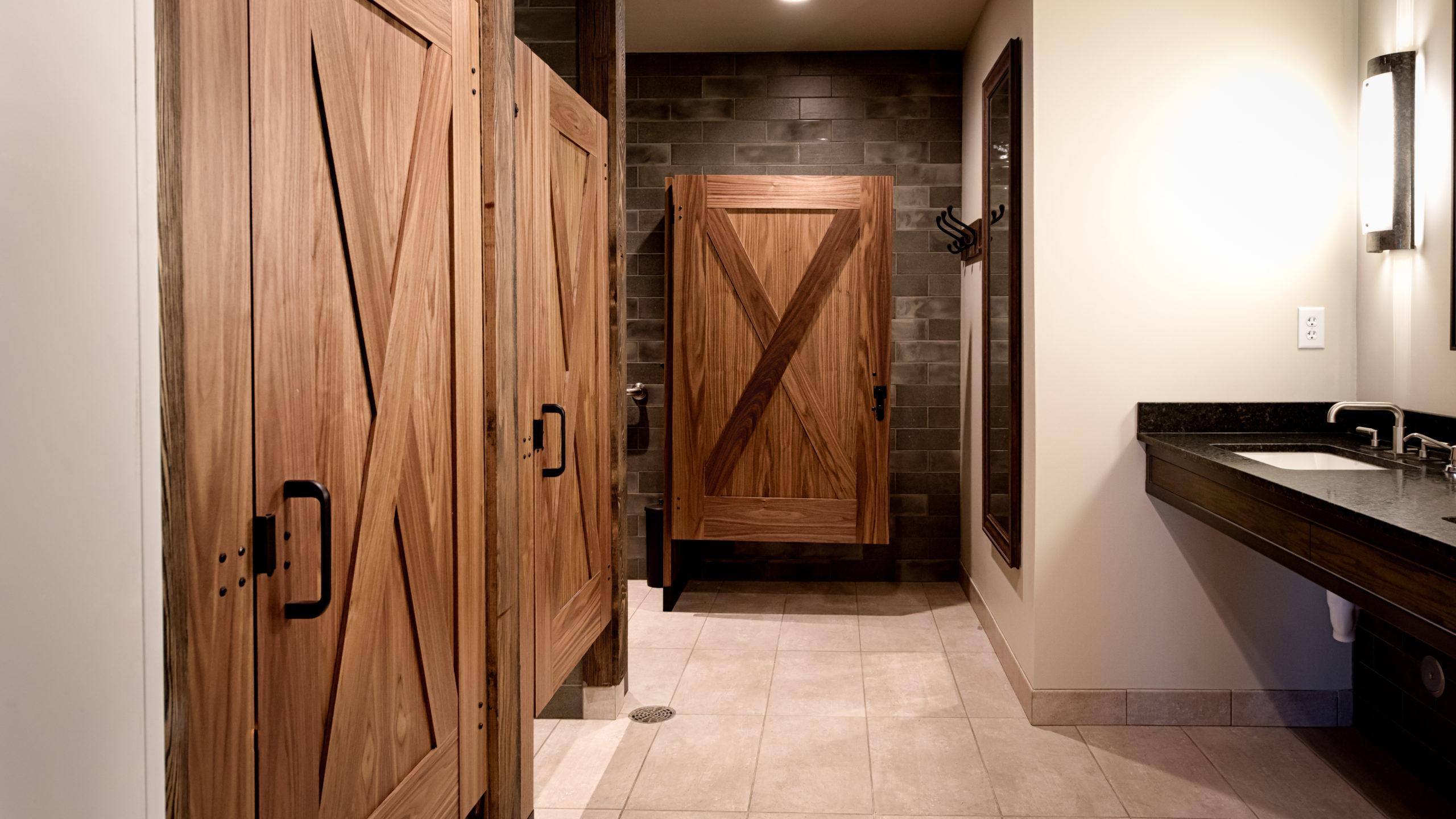 Luxury Montana lodge bathroom displaying three wood veneer captured panel doors with large X shape on both sides of doors in dark subway tiled room.