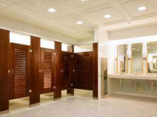 Elegant reception venue bathroom with coffered ceiling showing wood veneer pilasters and five louver doors with three gold rimmed mirrors over vanity.